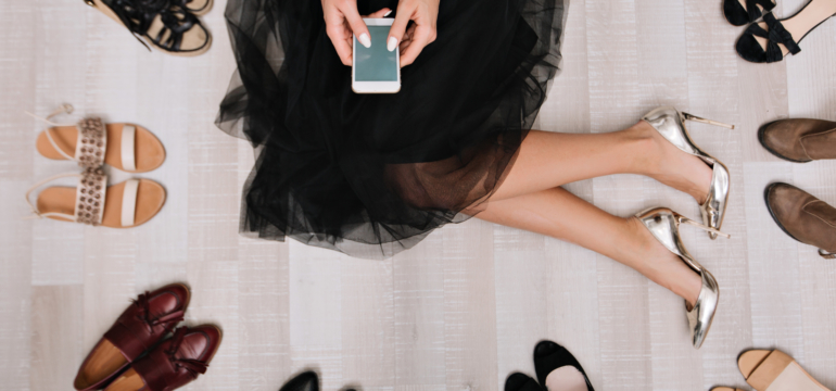 Stylish girl sitting on the floor in a dressing room with smartphone in hands, writes the message, surrounded by a variety of shoes. She is dressed in a black skirt, on her feet silver luxury shoes.